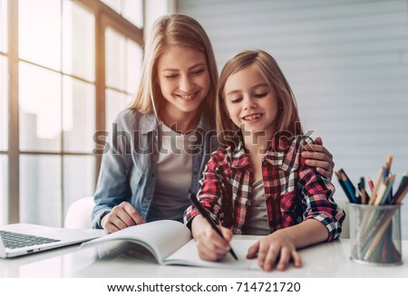 Attractive young woman and her little cute daughter are sitting at the table and doing homework together. Mother helps daughter with her school classes. #714721720
