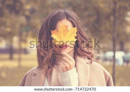 Beautiful Autumn Woman with Autumn Leaves on Fall Nature Background #714722470