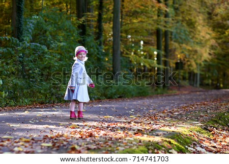 Beautiful little girl in blue coat playing in the park on a sunny autumn day. Children enjoying fall and jellow leaves. Family walking in the forest. #714741703