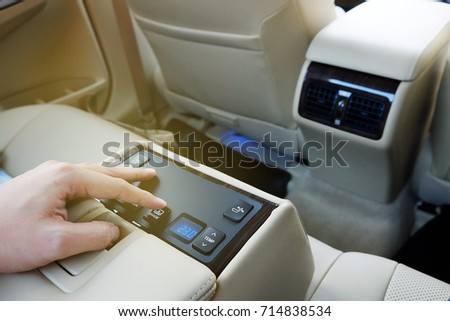 a finger push button to control electronic devices in back seat of  luxury car. #714838534