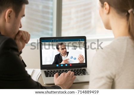 Businesspeople participate video conference looking at laptop screen during virtual meeting with investor for startup, discussing financial document online, videocall webcam app for business, close up #714889459