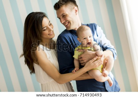 Portrait of mother and  father with cute little baby girl daughter against wall #714930493