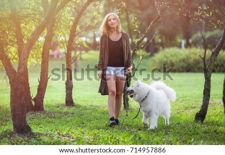 Young girl walking samoyed dog at the park outdoor #714957886