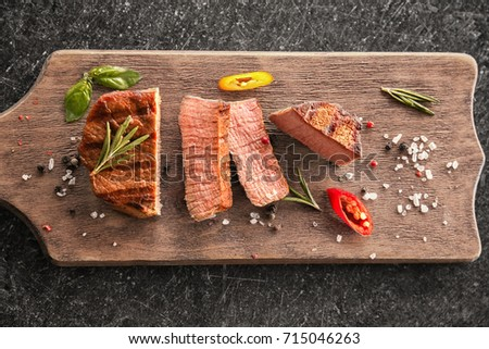 Board with tasty sliced steak on table #715046263
