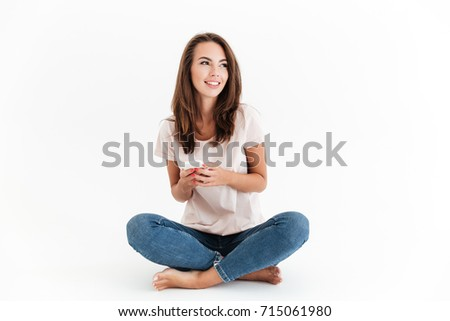 Pleased brunette woman sitting on the floor with smartphone in hands and looking away #715061980