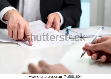 Signing a contract or agreement. Banker or lawyer showing client the line for autograph in a document paper. Business man with a customer in office making deal. Employee hired. Royalty-Free Stock Photo #715081804