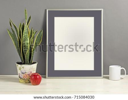 Silver frame mockup with plant pot, mug and apple on wooden shelf. Empty frame mock up for presentation design. Template framing for modern art. #715084030