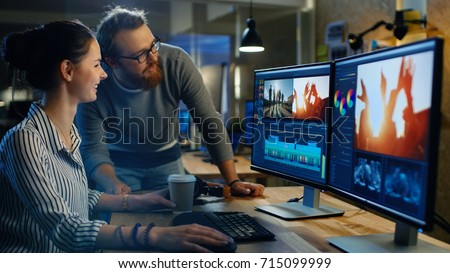 Female Video and Sound Editor Works With Her Male Colleague on a Project on Her Personal Computer with Two Displays. They Work in a Creative Loft Office.