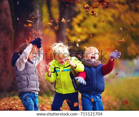 happy friends, schoolchildren having fun in autumn park among fallen leaves #715121704