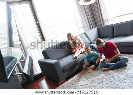 Happy family. Father, mother and children playing a video game Father and son playing video games together on the floor #715129516