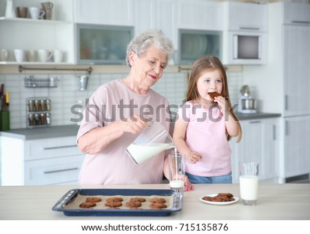 Cute little girl and her grandmother with cookies on kitchen #715135876