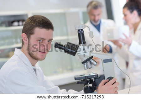 young male scientist with a microscope checking his sample #715217293