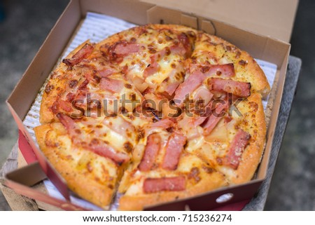 Top view of tasty pizza with ham, tomatoes, cheese and pineapple in box #715236274