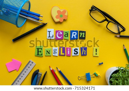 Word LEARN ENGLISH made with carved letters onyellow desk with office or school supplies, stationery. Concept of English language courses Royalty-Free Stock Photo #715324171