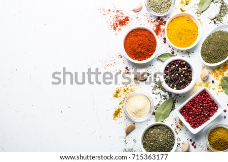 Set of various spices in a bowls on white background. Top view copy space. Royalty-Free Stock Photo #715363177