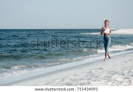 Runner woman running in the beach at sunset. Athletic fitness woman running on the beach. Outdoor workout. #715434091