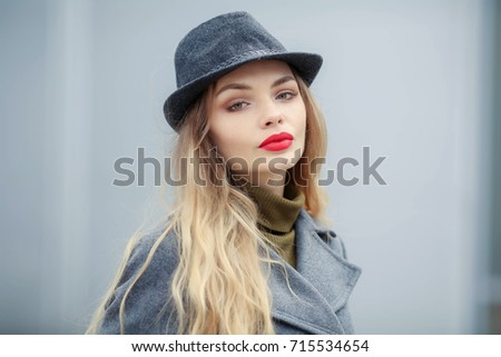 Beautiful young woman with red lips in hat and coat #715534654