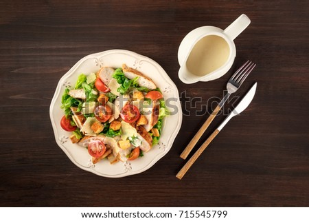 An overhead photo of a plate of chicken Caesar salad on a dark rustic background with a gravy boat, a fork and a knife, and copy space #715545799