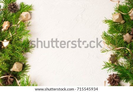 Christmas or New Year background: fir tree branches, gold glass balls, decoration and cones on a white plaster background #715545934