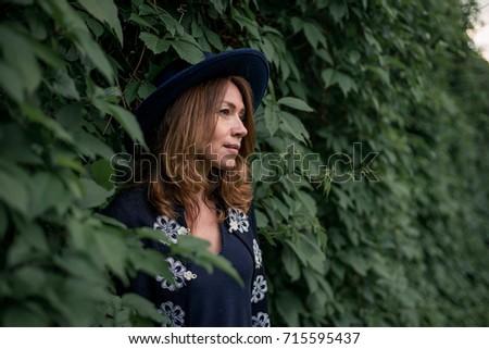 Closeup of beautiful woman against greenery garden wall #715595437