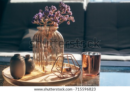 Home interior decor in gray and brown colors: glass jar with dried flowers, vase and candle on the wooden tray on the coffee table over sofa. Living room decoration. #715596823