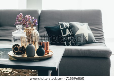 Home interior decor in gray and brown colors: glass jar with dried flowers, vase and candle on the wooden tray on the coffee table over sofa with cushions. Living room decoration. #715596850