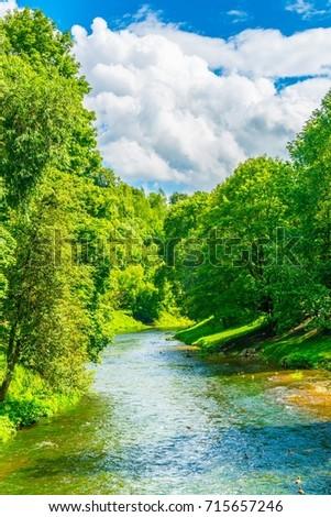 View of a creek passing next to the bernardine garden - bernardinu sodas in the lithuanian capital Vilnius.  #715657246