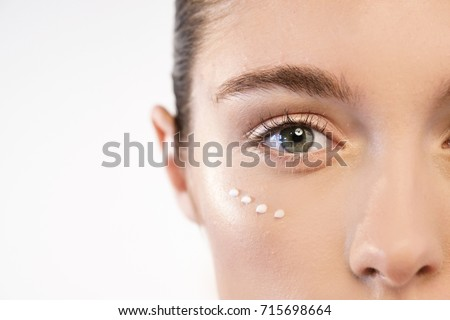 Close up of the face of a beautiful woman with perfect skin thanks to creams to keep young and cream contour anti-aging and wrinkle eyes. Concept of: beauty, cleanliness and perfection Royalty-Free Stock Photo #715698664