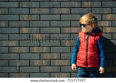 Cute fashionable boy standing in front of the brick wall. #715717597