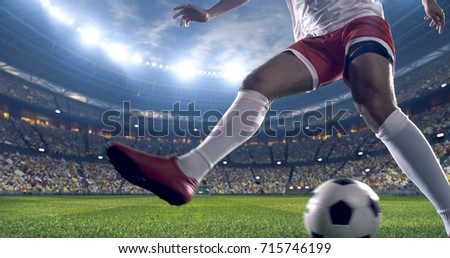 Soccer player kicks the ball on the soccer stadium. He wear unbranded sports clothes. Stadium and crowd made in 3D. #715746199