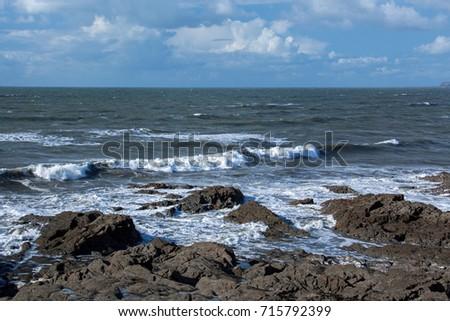 Waves crashing on the shoreline rocks #715792399