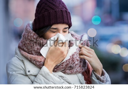Pretty young woman blowing her nose with a tissue outdoor in winter. Young woman getting sick with flu in a winter day. Woman with a cold. Royalty-Free Stock Photo #715823824