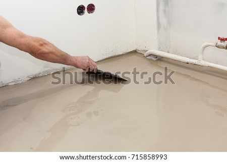 Worker pouring concrete on the floor use a spatula to level the solution. #715858993