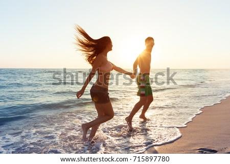 Happy young couple enjoying the sea #715897780