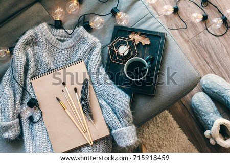 Still life details. Cup of coffee on rustic wooden tray, sketchbook and warm woolen sweater on sofa, decorated with led lights, top view point. Autumn weekend concept. Hobby and crafts. Royalty-Free Stock Photo #715918459