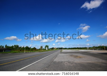 Black road with white lines under clouds in blue sky #716016148