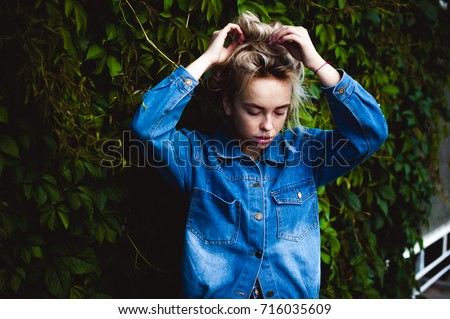 young beautiful woman in jeans clothes outdoors. portrait of a girl with freckles on her face, stylish girl against background of green leaves of a climbing plant, on a sunny summer autumn day. #716035609