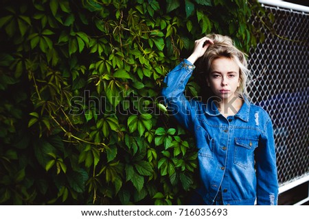 young beautiful woman in jeans clothes outdoors. portrait of a girl with freckles on her face, stylish girl against background of green leaves of a climbing plant, on a sunny summer autumn day. #716035693