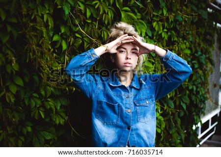 young beautiful woman in jeans clothes outdoors. portrait of a girl with freckles on her face, stylish girl against background of green leaves of a climbing plant, on a sunny summer autumn day. #716035714