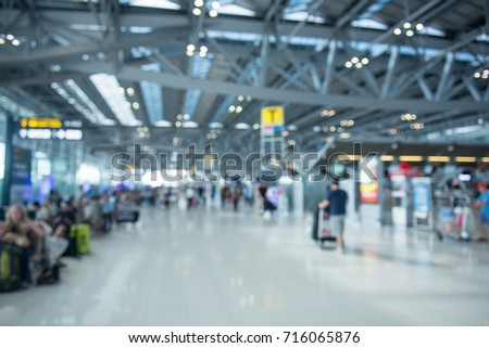 Traveling concept. Travelers asian walking with a luggage at airport terminal and airport terminal blurred crowd of Travelling people on the Background. Royalty-Free Stock Photo #716065876
