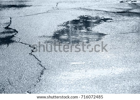 water puddles with raindrops and water circles on cracked wet asphalt road #716072485