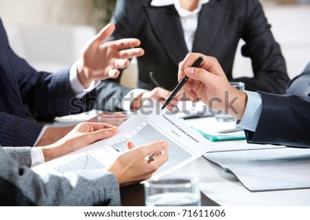 Close-up of businessman explaining a financial plan to colleagues at meeting Royalty-Free Stock Photo #71611606