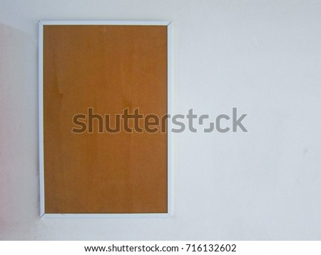 Blank brown picture frame on a white wall background, soft focus #716132602