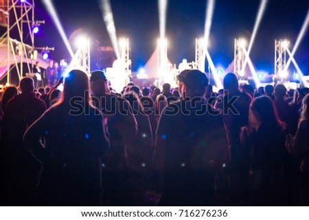 Crowd raising their hands and enjoying great festival party. Rock concert, silhouettes of happy people raising up hands. concert crowd - time exposure at a concert . Dark background. Soft focus #716276236