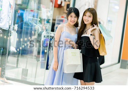 Two women are shopping in the shopping mall and they are so happy when her shopping. #716294533
