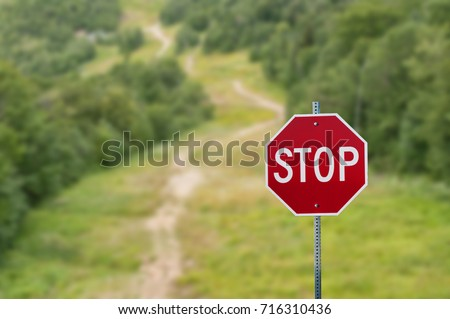 Stop sign against green forest trail background