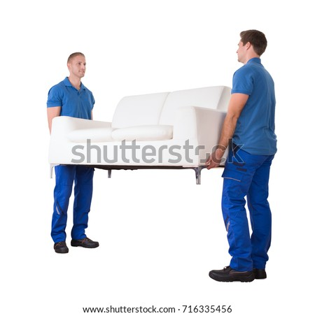 Two Young Movers Moving White Sofa In New Home Against White Background