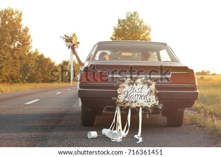 Happy wedding couple in decorated car #716361451