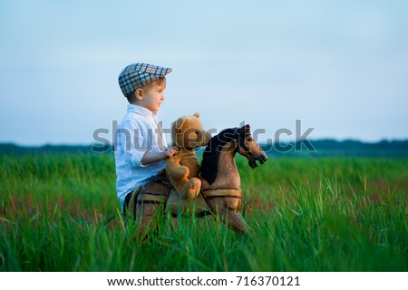 Child and horse. A small four year-old boy stands in the grass on a meadow with a horse and a teddy bear. #716370121