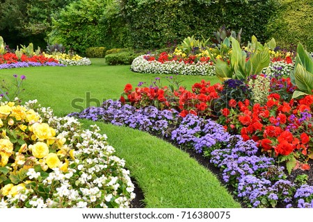 Scenic View of Colorful Flowerbeds with a Winding Grass Lawn Pathway through an Attractive Landscape Garden #716380075